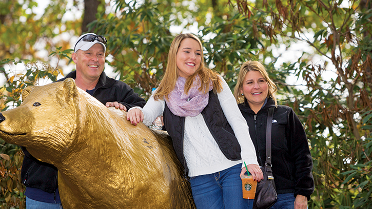 Student with parents and golden bear statue.